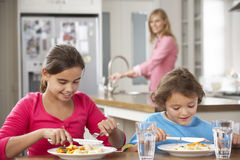 Two Children With Mother Having Meal In Kitchen Together Stock Photo