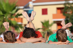 Two children with mother sleep. Two children with   mother sleep on  beach on  stomach, heaved up feet upwards and crossed them, focus on legs Royalty Free Stock Photos