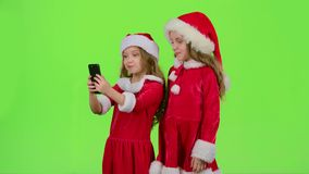 Two children in New Year costumes do selfie on the phone. Green screen. Two children in New Year costumes do selfie on the phone and make faces and grimaces stock video footage