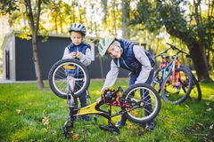 Two children, older boys and younger brother learning repair bike. Two guys siblings in helmets and single clothes use pump tool stock image