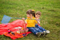 Free Two Children On A Picnic - A Boy In A Blue T-shirt Eats An Apple, And A Girl In A Yellow Catches A Net Of Insects Stock Photography - 181706302