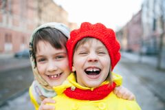 Two children outdoors in early spring. Two little sisters in winter city royalty free stock photography