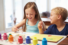 Two Children Painting Picture At Home Stock Photo