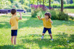 Two children in the park blowing and chasing soap bubbles and ha Royalty Free Stock Photos