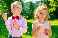 Two children in a park with soap bubbles Royalty Free Stock Photography