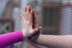 Sad punished kids. Two children parry their hands through a fence stock image