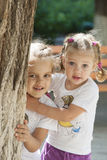 Two children peep out from behind a tree Stock Image