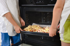 Two children placing homemade pizzas in the oven Stock Image