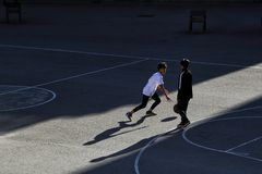 Two children play basketball on a street sports field stock photos
