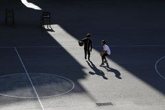 Two children play basketball on a street sports field stock photo