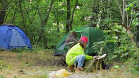 Two children play in the clearing near the tents in the forest. Camping in the forest. The elder sister and the little boy are playing in a clearing in the stock video