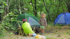 Two children play in the clearing near the tents in the forest. Camping in the forest. The elder sister and the little boy are playing in a clearing in the stock video footage