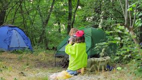 Two children play in the clearing near the tents in the forest. Camping in the forest. The elder sister and the little boy are playing in a clearing in the stock footage
