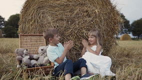 Two children play in a field under bundles of straw. A boy and a girl have fun walking in the field. Two children play in a field under bundles of straw. A boy stock footage