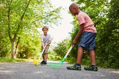 Two children play hockey as sport. Two children play street hockey together as sport in summer vacation royalty free stock photography