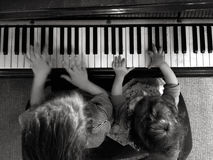 Two children play music on piano Stock Photography