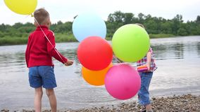 Two children play on the river Bank. Throw stones, make splashes of water. Beautiful summer landscape. Two children play on the river Bank. Throw stones, make stock video footage