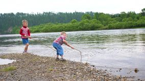 Two children play on the river Bank. Throw stones, make splashes of water. Beautiful summer landscape. Two children play on the river Bank. Throw stones, make stock video
