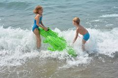 Two children play on the sea beach with crocodile - air bed. Two children play on the sea beach with green crocodile - air bed Royalty Free Stock Images