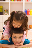 Two children playing. Two happy children playing on the floor Stock Photo