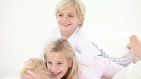 Two children playing on the back of their mother. In bed stock video