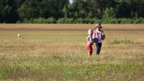 Two children playing with a ball in the field stock footage