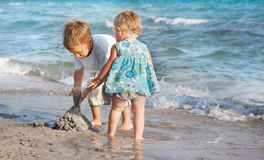 Two children playing on beach Stock Images