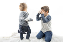 Two children playing at being photographers. Children playing with photographs Isolated background Royalty Free Stock Photos