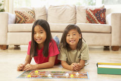 Two Children Playing Board Game At Home. In Lounge stock photography