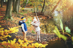 Two children playing with branch near pond Stock Photo
