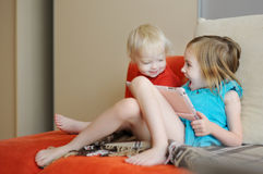 Two children playing on a digital tablet Stock Images