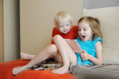 Two children playing on a digital tablet Royalty Free Stock Photos