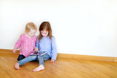 Two children playing on a digital tablet Stock Photos