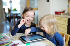 Two children playing with a digital tablet at home Royalty Free Stock Images