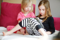 Two children playing with a digital tablet at home Royalty Free Stock Image