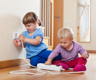 Two children playing with electrical extension stock images