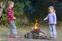 Two children playing with fire on natural backgroun royalty free stock images