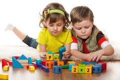 Two children are playing on the floor stock photos