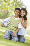 Two children playing football in park Stock Images