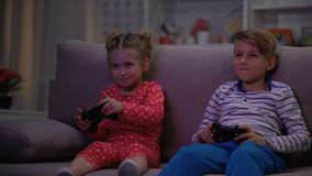 Two children playing game with joysticks caught parents at night, entertainment. Stock footage stock video