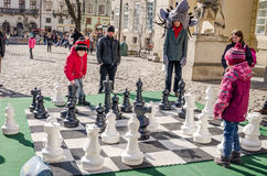 Two children playing in a huge moving chess pieces on the board at the central Market Square in Lviv, people look around them at t Stock Images