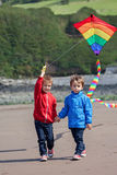 Two children playing with a kite on the beach Stock Photos