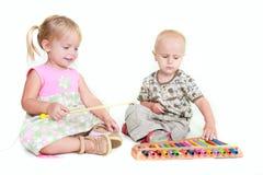 Two children playing music piano