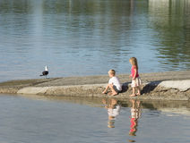 Two children playing near water on boat ramp. Royalty Free Stock Photo