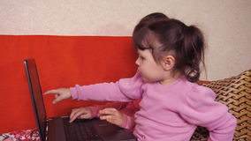 Two children playing in a notebook on an orange couch. Two girls sitting on the couch with a laptop stock footage