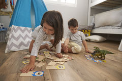 Two Children Playing Number Puzzle Game Together In Playroom Stock Photos