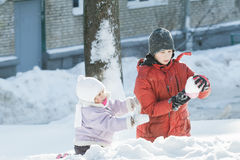 Two children playing outdoors with plastic toy tool in snowy winter sunny day Royalty Free Stock Photography