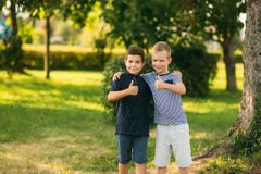 Two children are playing in the park. Two beautiful boys in T-shirts and shorts have fun smiling.  royalty free stock images