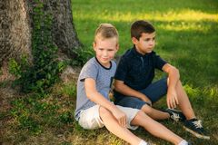 Two children are playing in the park. Two beautiful boys in T-shirts and shorts have fun smiling. They eat ice cream. Jump, run. Summer is sunny royalty free stock photography