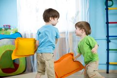 Two children playing with pillows Stock Image